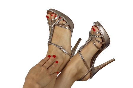 Female feet with sandals and red nail polish. Isolated on white background.