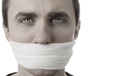 Young man with bandage covering his mouth on white Archivio Fotografico