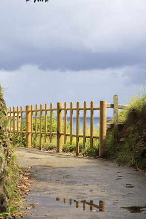 basque country: Fence in a footpath near the sea with rocks around. Stock Photo