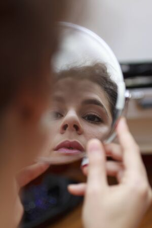 Young woman cheking her make-up in a rounded mirror. Foto de archivo