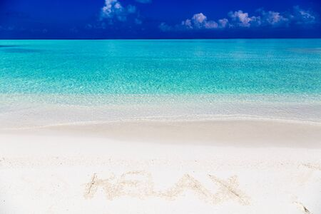 Word relax written on sand in Maldives with the lagoon at background. Stock Photo