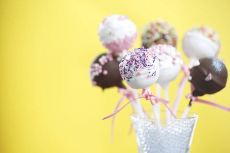 Cakepop over yellow background and space at the left.
