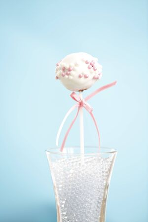 A single cakepop over blue background with pink ribbon.