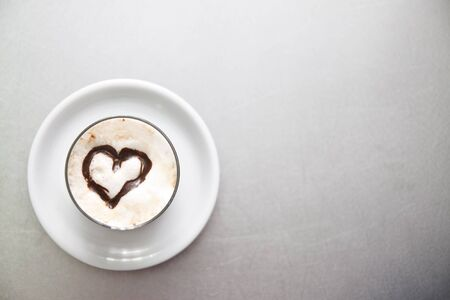 Cup of milk with a heart made with liquid chocolate. Stock Photo