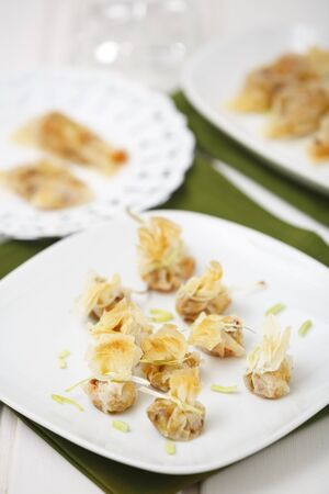 Bags made with filo pastry and folled with leek, onion an prawn. Stock Photo