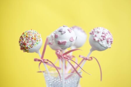 Cakepops over yellow background with pink ribbon.