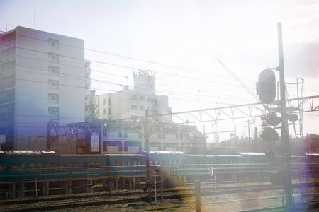 View from the deck of a train station in Tokyo while a train is approaching. Light leaks effect added. Stock Photo