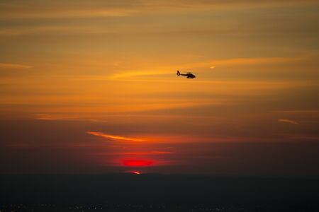 Silhouette of a helicopter against sun at dusk. Stock Photo