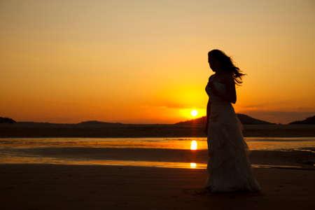 Bride contemplating beach at sunset. Low light Stock Photo
