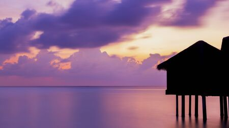 Gorgeous dusk in Maldives. Bungalows are black silhouette. Stock Photo