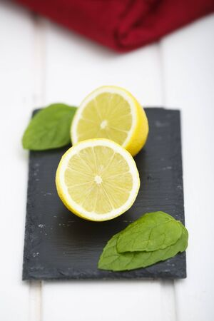 Lemon in halves on a blackboard with green leaves and red napkin.