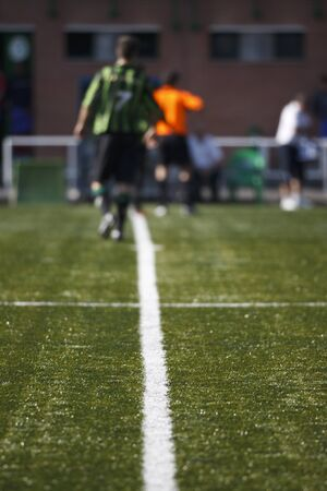 Detail of lines of soccer field with soccer players at background and out of focus.