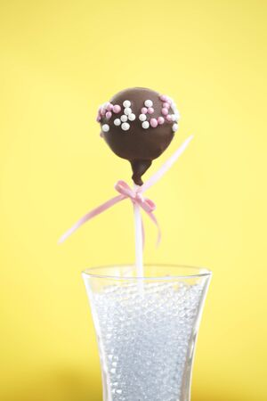 A single cakepop over yellow background.