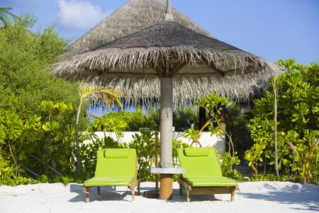 Two chairs and umbrella in the beach in Maldives.