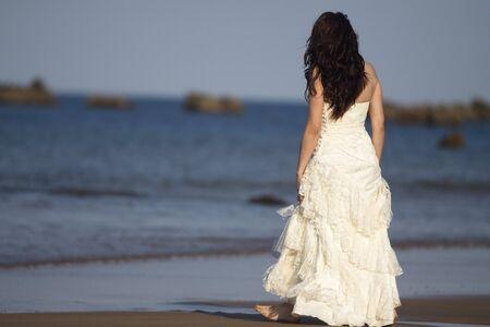 Bride walking in the beach.