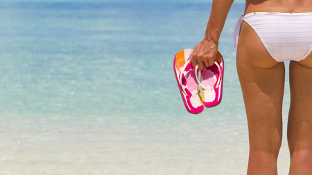 Woman holding flip flops while standing on the beach.