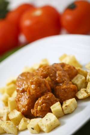 Meatballs with tomato sauce and fries around them.
