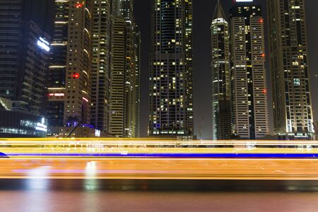 Boat full of light coming from the right of the frame and going to the left in the river at Dubai Marina in the night. Stock Photo