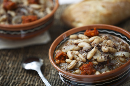 Stew of white beans with spicy sausage and bread.