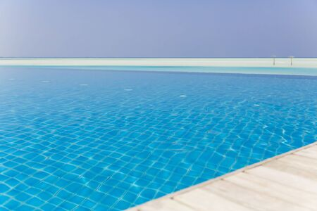 Beautiful shot from edge of a swimming pool with beach at background.
