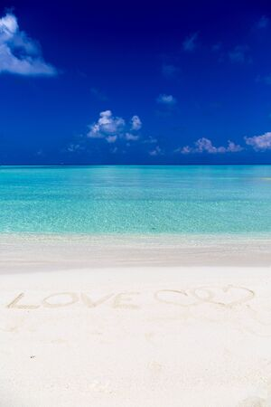 Word love written on sand in Maldives with the lagoon at background.