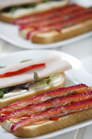 Delicious sandwich with gravlax, turkey and green vegetables. Stock Photo - 89325553