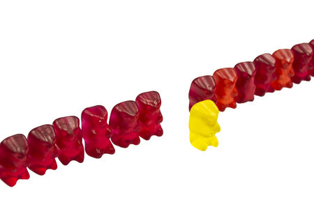 gummie: yellow Bear with other red Gummy Bears isolated on white