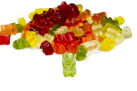 gummie: green bear with other multi colored gummy Bears isolated on white