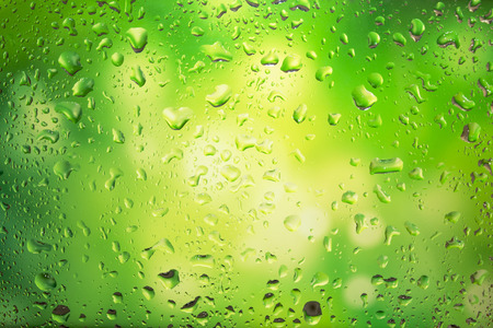 Water droplets on glass, bright green background photo