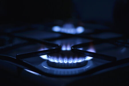 combust: Blue flames of gas stove in the dark. Shallow depth of field