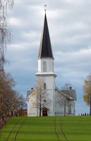 hillock: A wooden church staying on a hillock, overa a grass field, with an alleyway to one side. The church is situated in Fet, Norway.