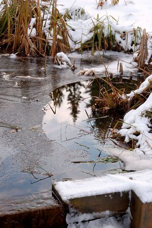 ice dam: A pond with a small dam, partly frozen over