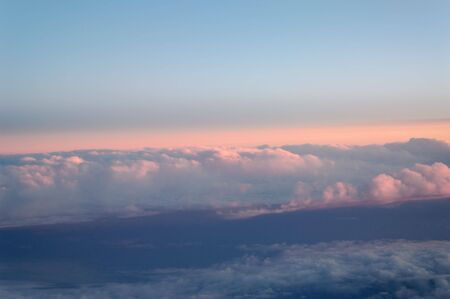 Clouds, lit pink from above by the setting sun, seen from an airplane.