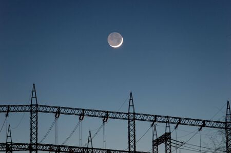 transformator: A crescent moon hanging lower of the power masts and lines of a transformator station.