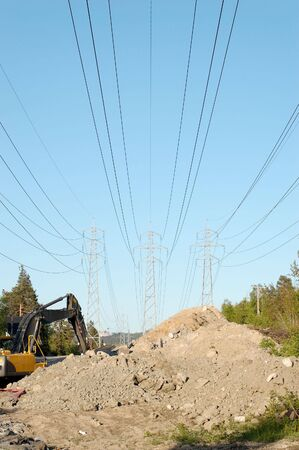 Three power masts supporting high voltage lines with a construction site and an excavator beneath