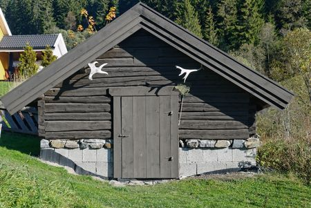 A small traditional Norwegian storage house or cellar, made of tared timber with moose horns.