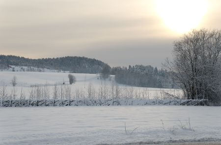 Partially clouded sky with the Sun shining through it, illuminating snowcovered fields, and a traditional Norwegian slanted fence.