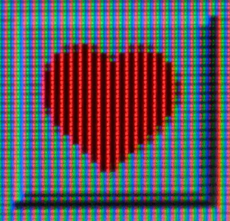 An extreme macro of an LCD screen, showing a red heart.