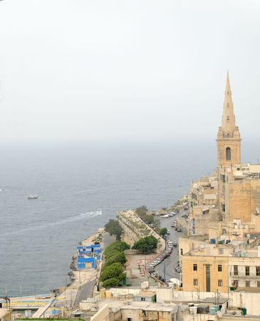 The spire of the StPauls Anglican Cathedral and the Germain Curtain of the Valetta battlements on Malta.