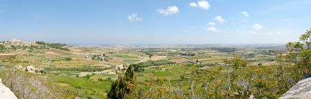 150 degree panorama of Maltese countryside with foreground vegetation. Stitched from 7 individual images shot at 18mm. The image is taken from Mdina.
