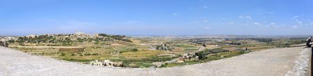 180 degree panoramic image of Maltese countryside and Mosta as seen from Mdina battlements. The image is composed from 13 stitched exposures. In the middle of the sky and airplane goes in for landing.