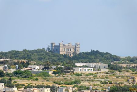 View on Verdala Palace as seen from Dingle Cliffs at 2km distance through the heat haze of Southern Maltese countryside.