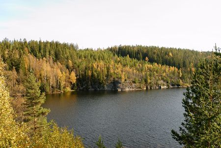 A lake, framed by autumn coloured forest on mountain sides.