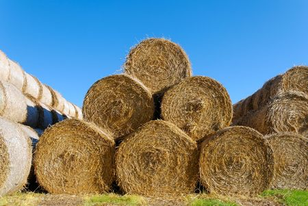 A pyramid of 6 hay bails, lit by high autumn sun.  Stock Photo