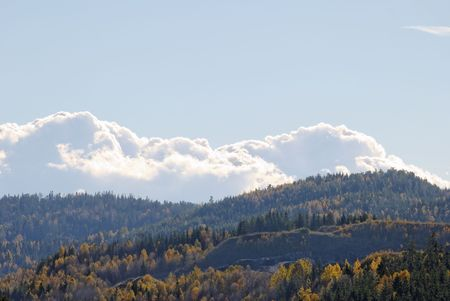 Billowing clouds over mountains clad in autumn-coloured forests  Stock Photo