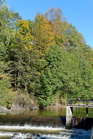 A river calmly flowing over a small dam with trees touched by autumn on its bank.
