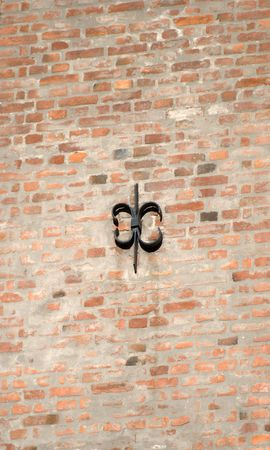 Cast iron fixture on sunlit brick wall.