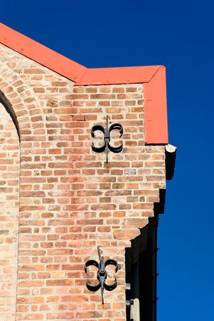 A corner of a brick house with two cast iron fixtures on polarised deep blue sky.  Stock Photo