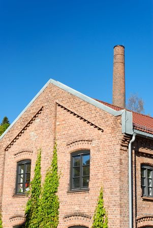 Old factory building on clear polarised blue sky with a chimney behind