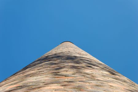 Brick factory chimney seen in perspective straight from below.